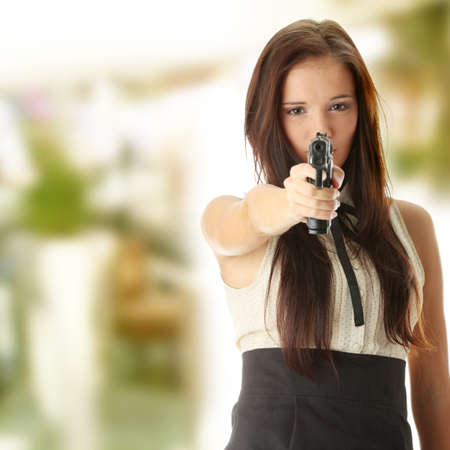 Young caucasian woman with hand gun  photo