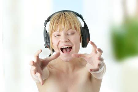 agressive: Young beautiful happy women listening agressive music in headphones