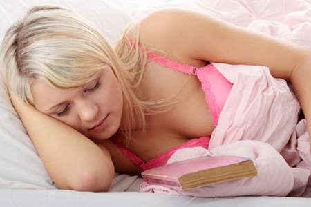 Beautiful young woman reading book in bed  photo