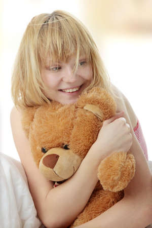 Charming blonde in bed embraces teddy bear photo