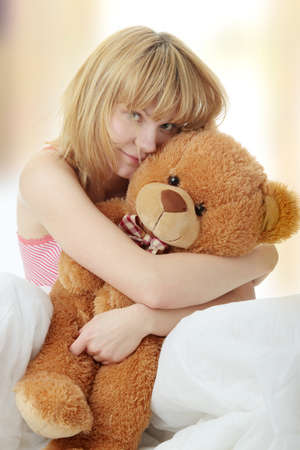 Charming blonde in bed embraces teddy bear Stock Photo - 6931942