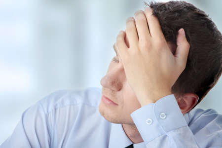 sick person: Businessman in depression with hand on forehead Stock Photo