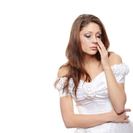 Beautiful young caucasian sad bride crying, over white background photo