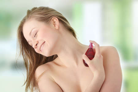 Sensual blond woman applying perfume on her body, isolated on white  photo