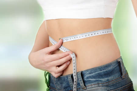 woman measuring waist: Sexy, fit, young woman measuring her waist