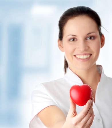 Giovane infermiera con il cuore in mano, isolato su sfondo bianco  Archivio Fotografico - 6955425
