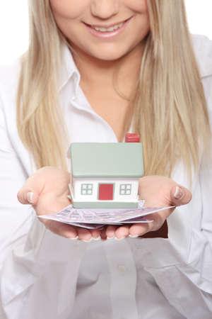 Beautiful young woman holding euros bills and house model over white photo