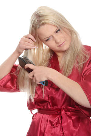 red bathrobe: Young blond woman is combing her hair and wearng red bathrobe  Isolated on white