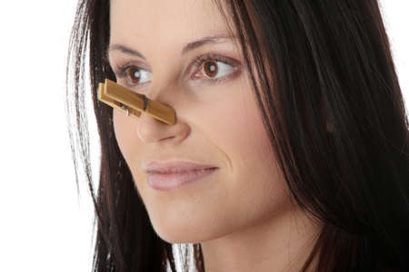 stinky: Portrait of young caucasian woman with Clothespin on her nose - bad smell concept