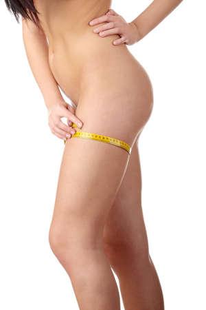 cintura perfecta: La chica linda mide su cuerpo sobre un fondo blanco. Concepto de estilos de vida saludables. Foto de archivo