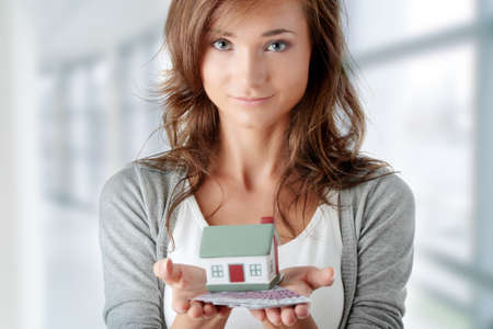 owning: Beautiful young woman holding euros bills and house model over white - real estate loan concept