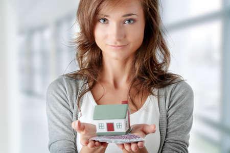 courtier: Belle jeune femme tenant des factures euros et mod�le de maison sur blanc - concept de pr�t immobilier Banque d'images