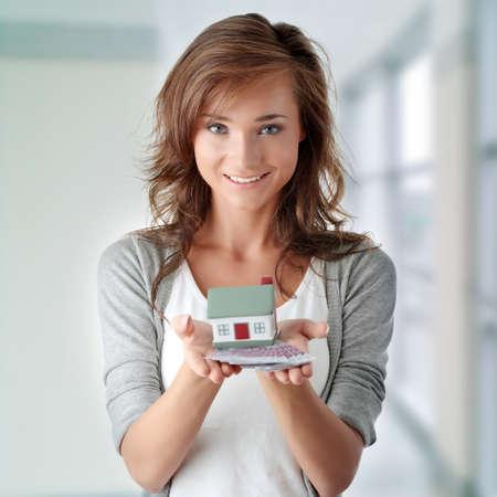 agent de s�curit�: Belle jeune femme tenant des factures euros et mod�le de maison sur blanc - concept de pr�t immobilier Banque d'images