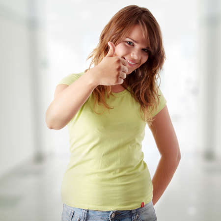 Young woman showing OK. Looking at camera and smiling. photo