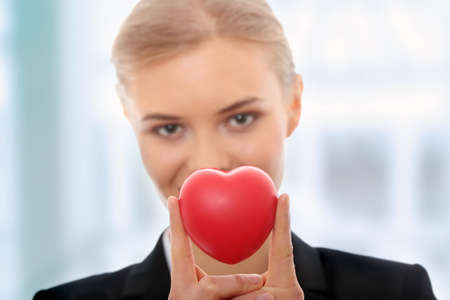 business protection: Young business woman holding heart shaped toy
