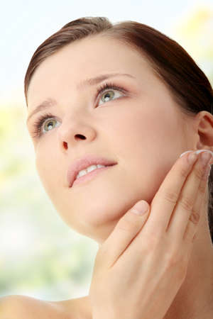 Woman applying moisturizer cream on face. Close-up fresh woman face. Stock Photo - 7509752
