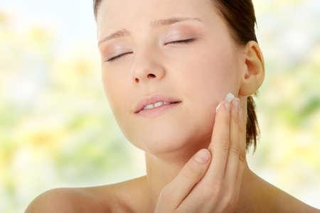 Woman applying moisturizer cream on face. Close-up fresh woman face. Stock Photo - 7509747