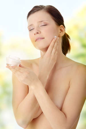 Woman applying moisturizer cream on face. Close-up fresh woman face. Stock Photo - 7509749