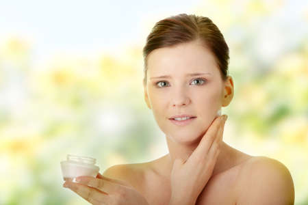 humidify: Woman applying moisturizer cream on face. Close-up fresh woman face.