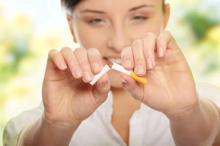 Young woman breaking cigarette over white background Stock Photo