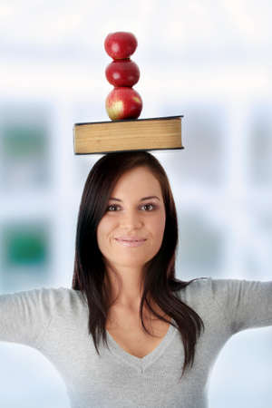 Beautiful student woman have book and apple on her head - learning concept photo