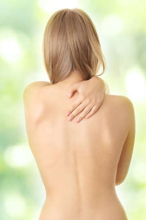 Woman from behind, naked body, pain concept,against abstract green background photo