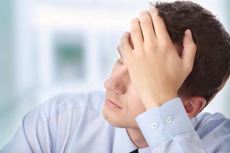 worry: Businessman in depression with hand on forehead Stock Photo
