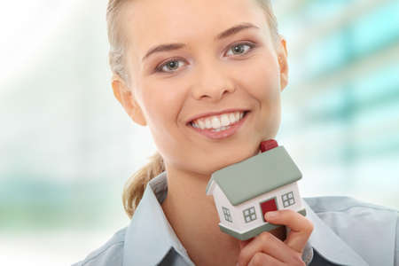 Young beautiful business woman with house model - real estate photo