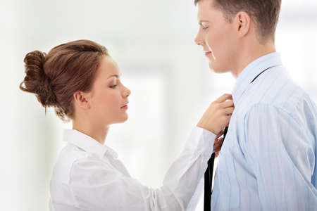 Businesswoman knotting the necktie of the businessman, helping and assisting him getting dressed.  photo