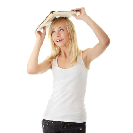 Teen girl with book over her head, isolated on white photo