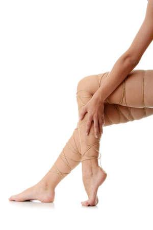 Beine Schmerz Konzept - Beine gebunden mit Seil, isoliert auf weiss