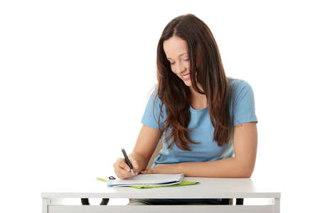 Teen girl learning at the desk, isolated on white   photo