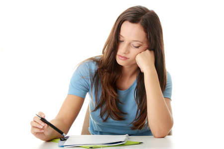 struggles: Teenage girl studying at the desk being tired, isolated on white   Stock Photo