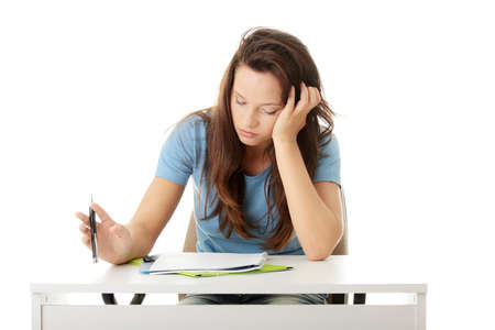 Teenage girl studying at the desk being tired, isolated on white   Stock Photo