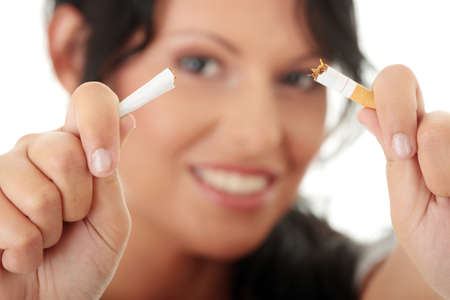 quiting smoking: Young woman quiting smoking, isolated on white - focus on hand Stock Photo