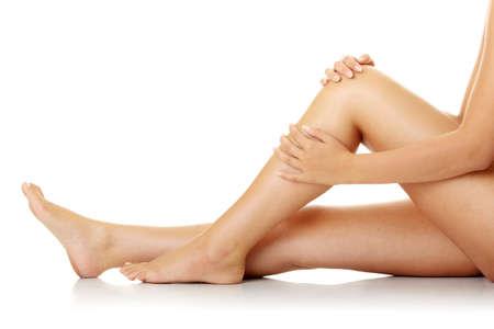 cramp: Knee Injury. Woman holding on sore knee.  Stock Photo