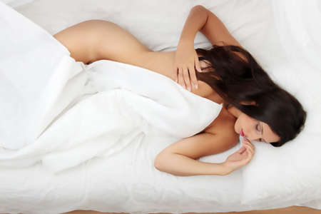 Closeup portrait of a cute young woman sleeping on the bed Stock Photo - 8048288