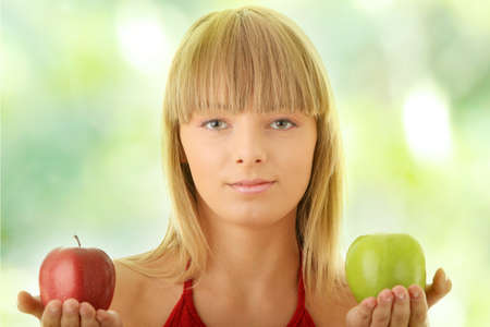 Young blond woman with red and green apples on her hand - making decision concept photo