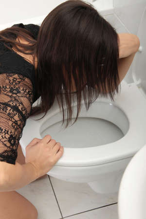 bulimia: Young woman in elegant dress vomiting  Stock Photo