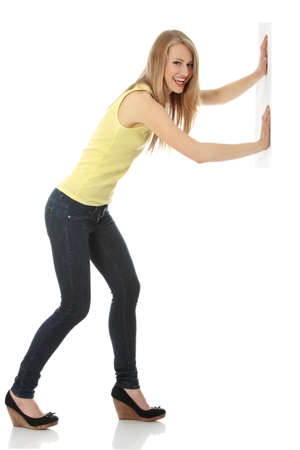 pushing: Woman pushing something imaginary isolated over a white background (white wall over her hands) Stock Photo