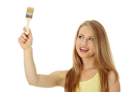 Beautiful blond woman painting something with paintbrush, isolated on white Stock Photo - 8719780