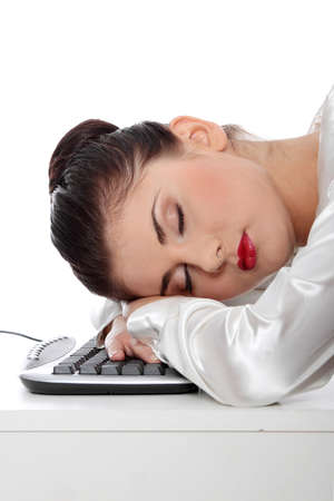 Young businesswoman sleeping on the keyboard in the office. Isolated on white  photo
