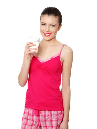 Young teen woman in pink pajama drinking milk , isolated on white Stock Photo - 8830484