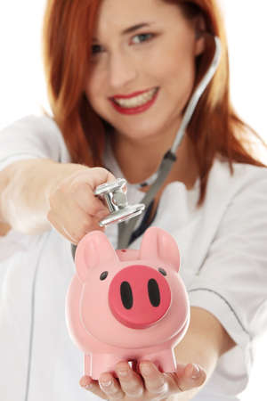 Curing finances concept. Young doctor trying to cure piggy bank photo