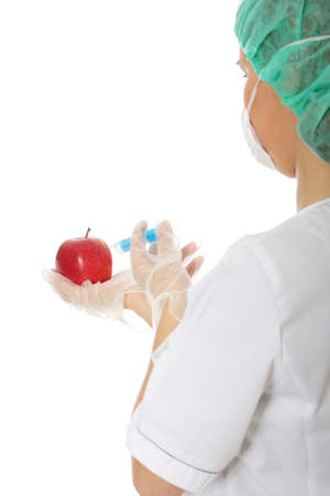 Woman in white coat with syringe and apple (biotechnologist). White background. Studio shot.  photo