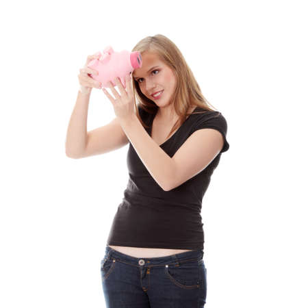 Young woman trying to get money from her piggy bank, isolated on white background Stock Photo - 8828146