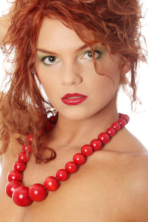 Close up portrait of beautiful redhead woman with big ,red,vintage, wooden beads photo