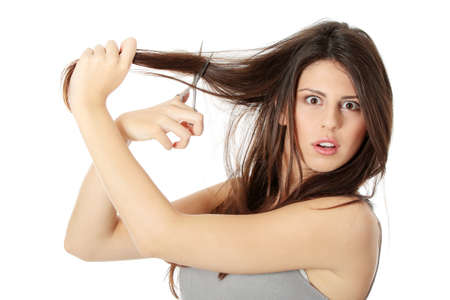 Young woman with scissors cutting her long hairs, isolated on white  photo