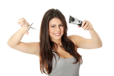 Young beautiful female hairdresser holding scissors and hair clipper, isolated on white Stock Photo - 8828180