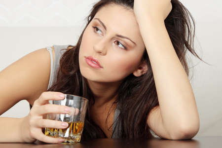 alcoholic beverages: Yound beautiful woman in depression, drinking alcohol